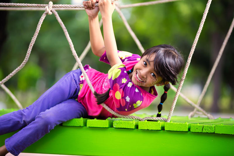 Lycklig liten asiatisk flicka på lekplatsen royaltyfri bild