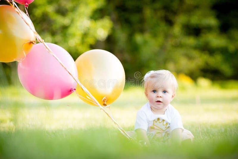Lycklig liten blond caucasian flicka utanför med ballonger royaltyfri bild