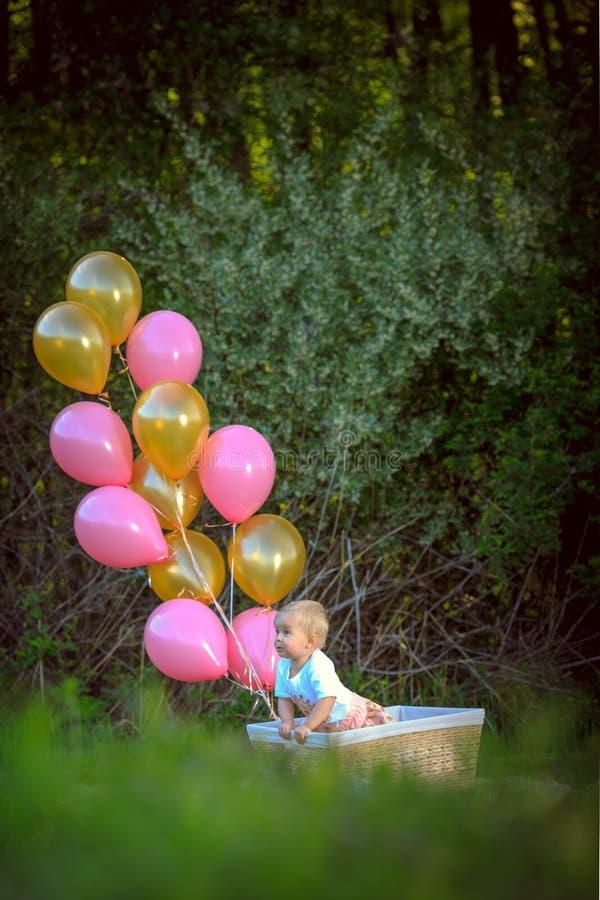 Lycklig liten blond caucasian flicka utanför med ballonger royaltyfria bilder