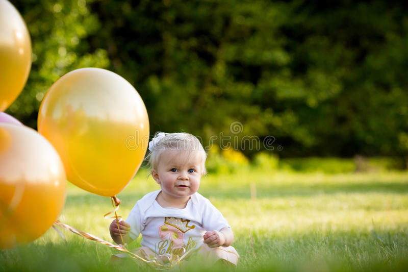Lycklig liten blond caucasian flicka utanför med ballonger royaltyfri fotografi