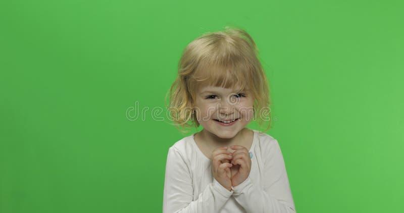 Lycklig liten blond flicka i den vita t-skjortan gulligt blont barn Danande v?nder mot royaltyfri foto