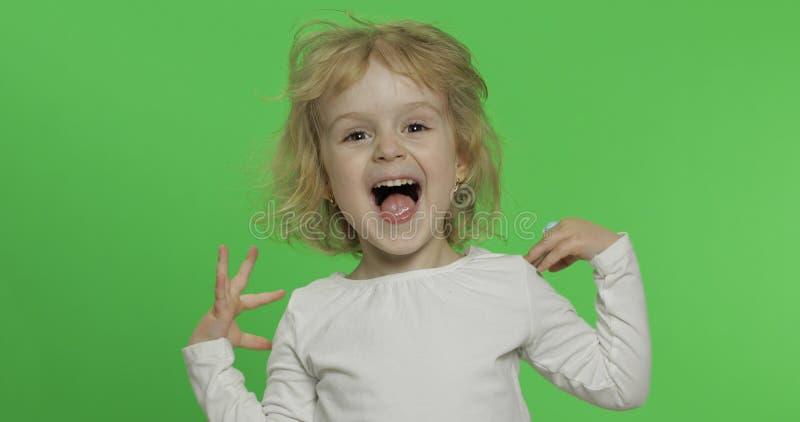 Lycklig liten blond flicka i den vita t-skjortan gulligt blont barn Danande v?nder mot royaltyfri bild