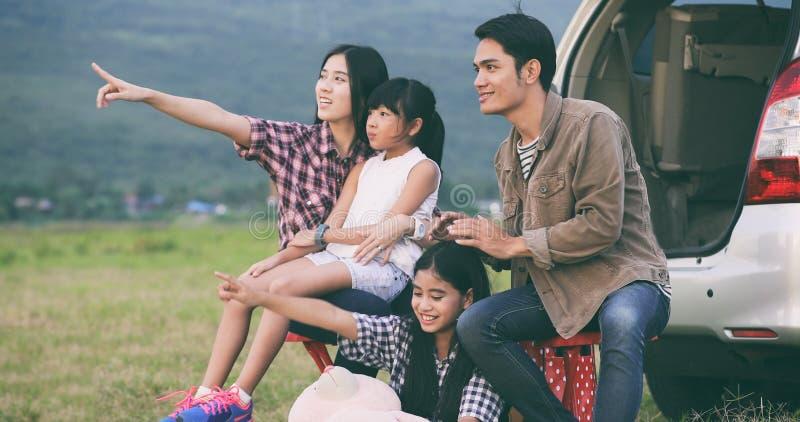 Lycklig liten flicka e med asiatiskt familjsammanträde i bilen för enj royaltyfri fotografi