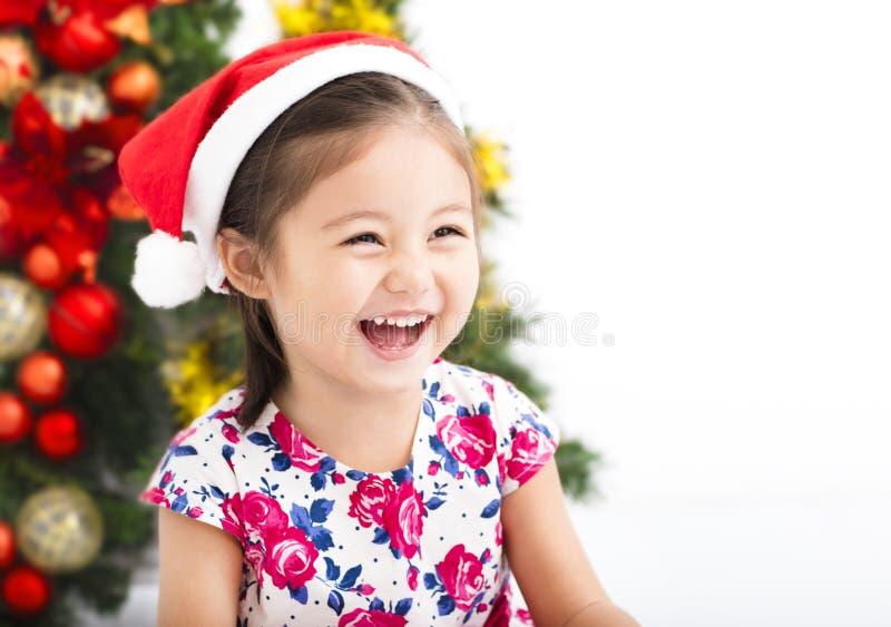 Lycklig liten flicka framme av julträdet arkivfoton