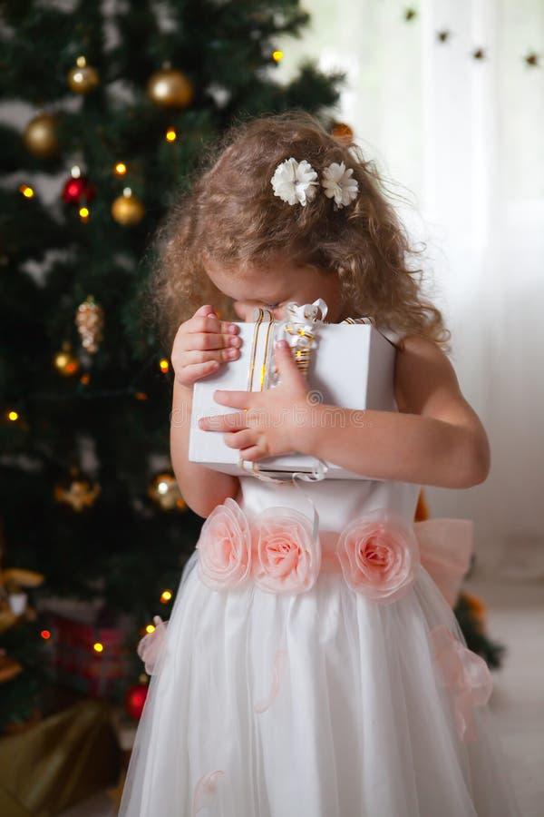 Lycklig liten flicka i den vita klänningen som kramar en ask med en gåva royaltyfri foto
