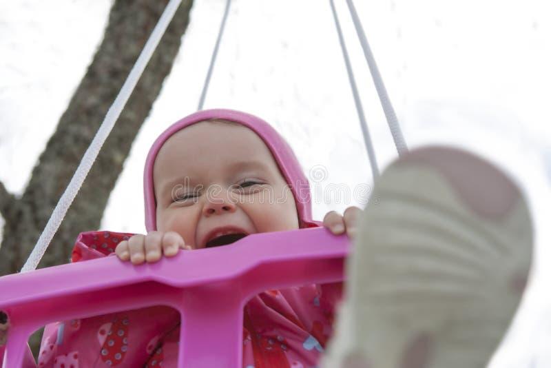 Lycklig liten flicka i en swing arkivbild