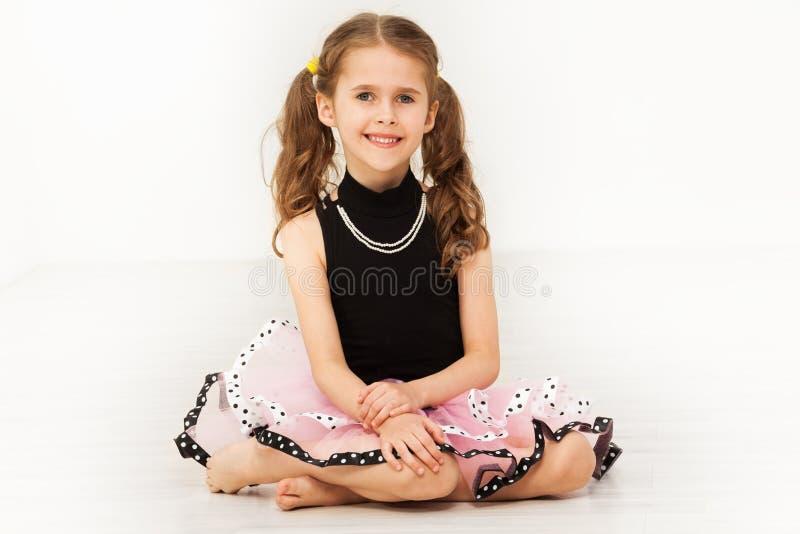 Lycklig liten flicka i härlig klänning och halsband royaltyfri foto