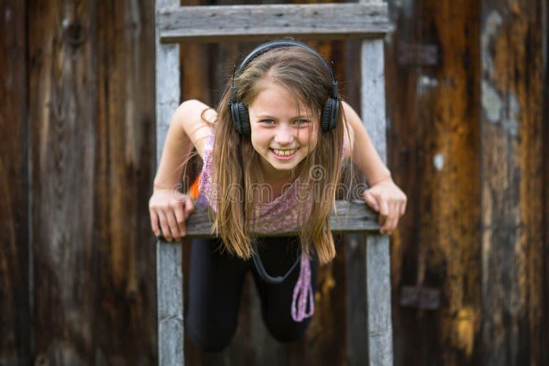 Lycklig liten flicka i hörlurar som spelar på trätrappan Lyckligt royaltyfria bilder