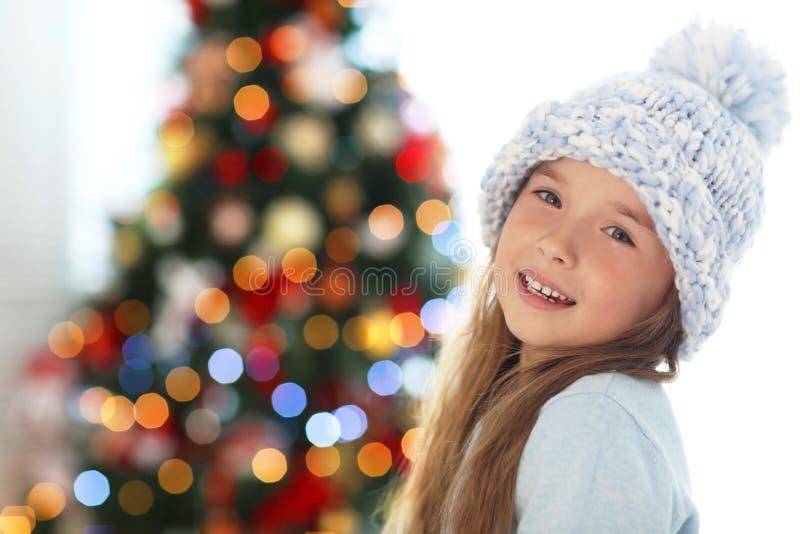 Lycklig liten flicka i hatt mot den suddiga julgranen arkivbilder