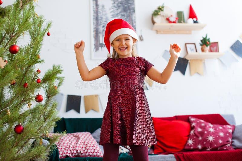 Lycklig liten flicka i röd klänning och jultomtenhatt som förväntar jul i röda garneringar arkivbilder