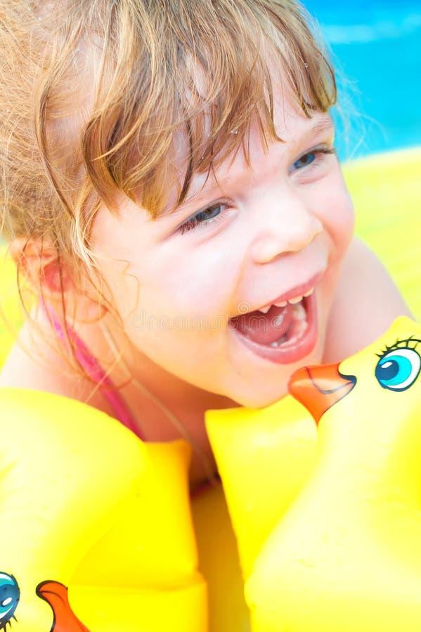 Lycklig liten flicka i simbassängen arkivbild