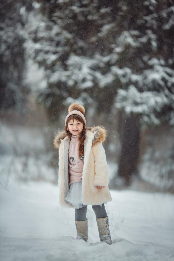 Lycklig liten flicka i snöig skog royaltyfri bild