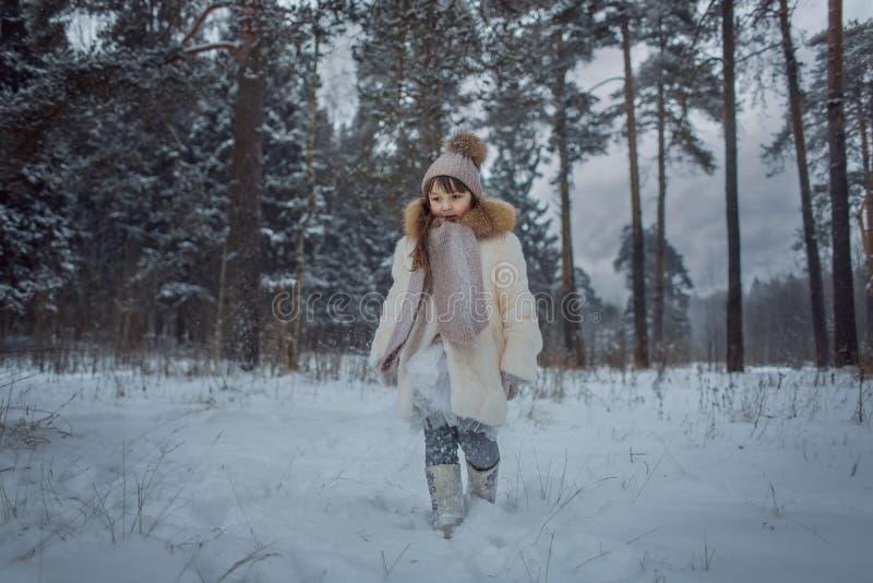 Lycklig liten flicka i snöig skog arkivfoton