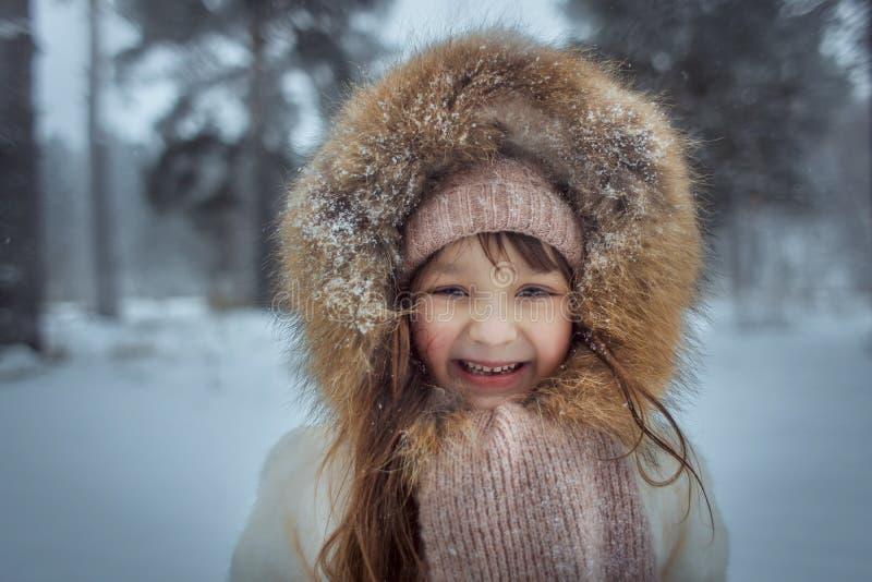 Lycklig liten flicka i snöig skog royaltyfri foto