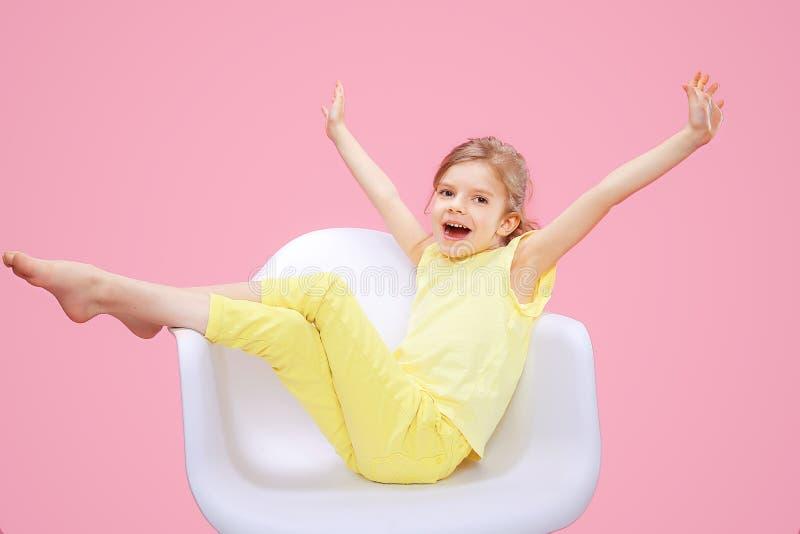 Lycklig liten flicka i stol arkivbild
