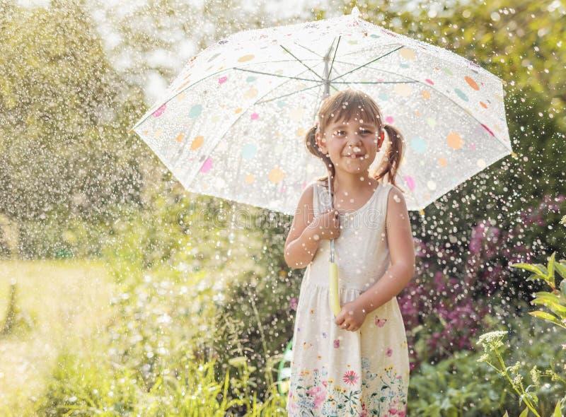 Lycklig liten flicka i trädgård under sommarregnet med ett paraply arkivfoto