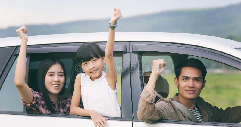 Lycklig liten flicka med asiatiskt familjsammanträde i bilen för enjo arkivfoto