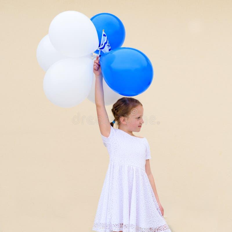 Lycklig liten flicka med bl?a och vita ballonger arkivfoto