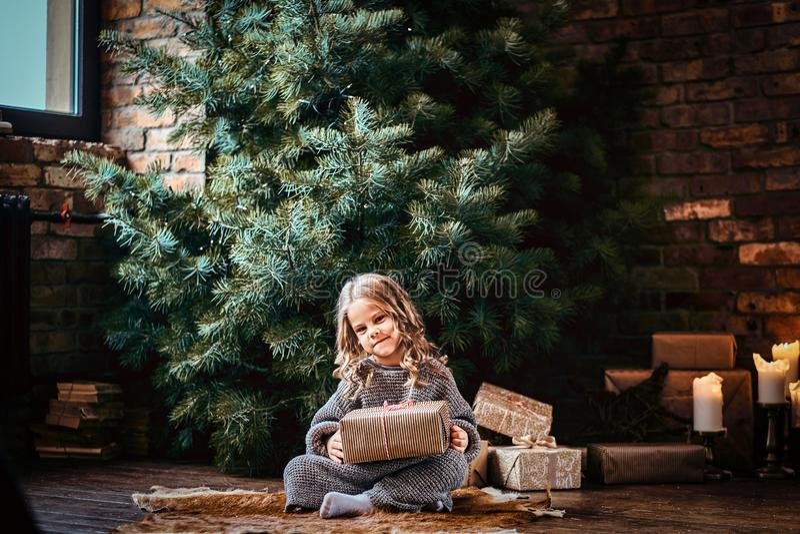 Lycklig liten flicka med blont lockigt hår som bär en varm tröja som rymmer en gåvaask, medan sitta på ett golv bredvid arkivbild