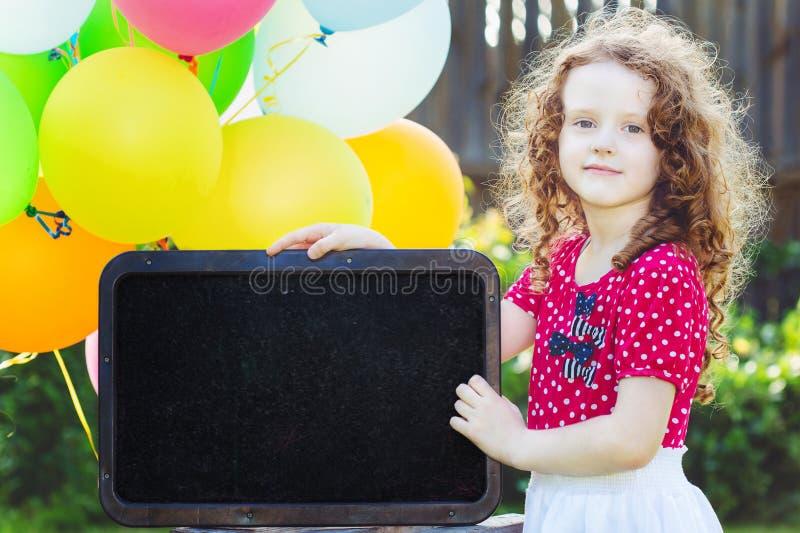 Lycklig liten flicka med brädet och den färgade ballongen Ställe för ditt royaltyfri fotografi