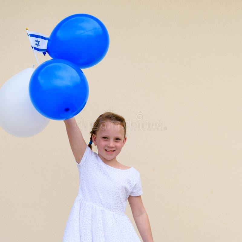 Lycklig liten flicka med den bl?a och vita flaggan f?r ballongans Israel royaltyfria foton