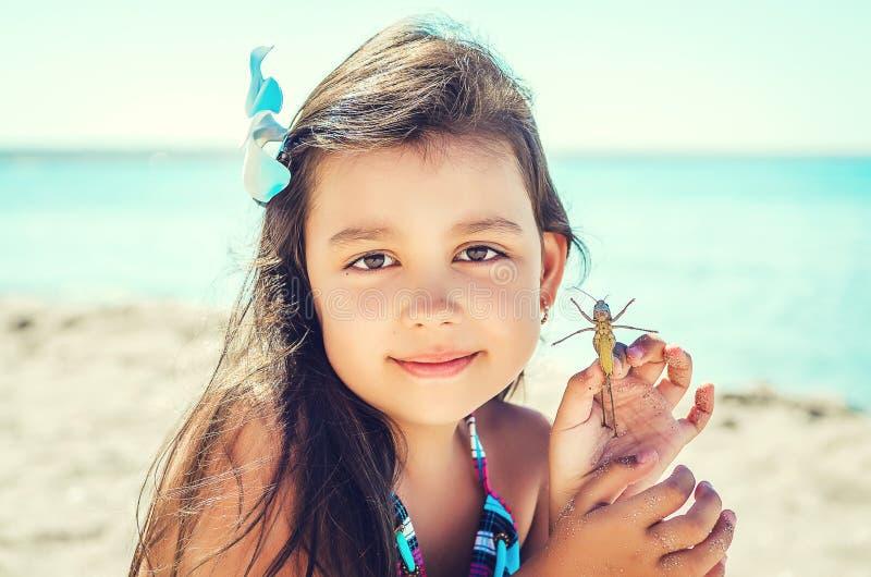Lycklig liten flicka med en gräshoppa royaltyfri foto