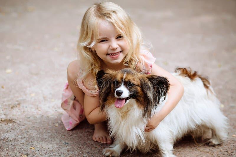Lycklig liten flicka med ett hundanseende på vägen i parkera Gullig liten flicka som kramar en hund som ler Barn med hundkapplöpn royaltyfri bild