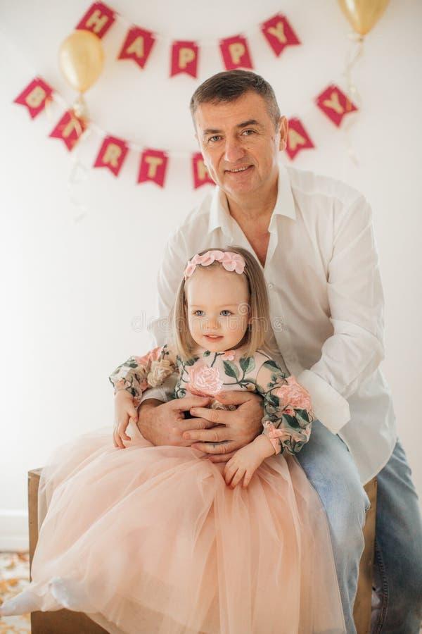 Lycklig liten flicka med fadern som firar födelsedagpartiet royaltyfria bilder