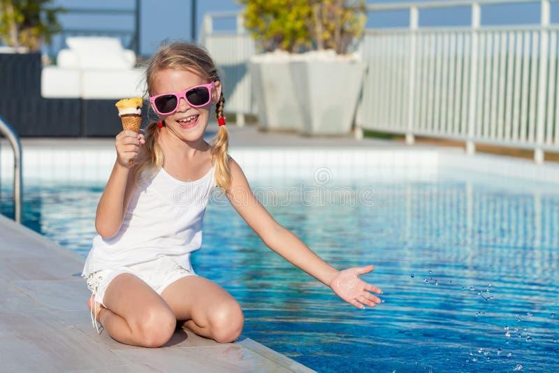 Lycklig liten flicka med glasssammanträde nära en simbassäng på royaltyfri foto