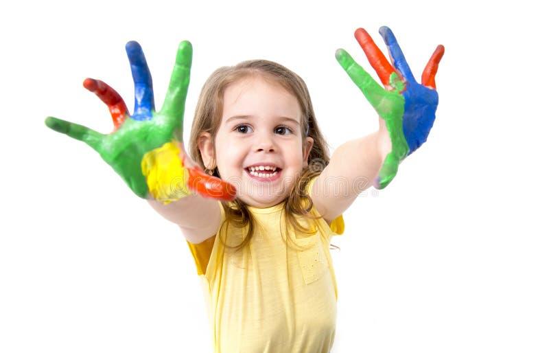 Lycklig liten flicka med händer som målas i färg arkivfoto