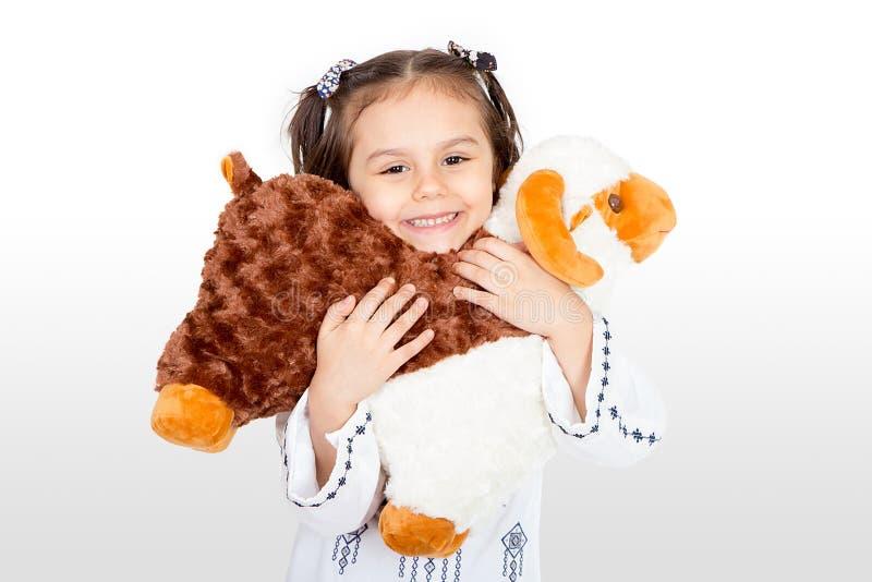 Lycklig liten flicka med hennes fårleksak - fira Eid ul Adha - royaltyfria foton