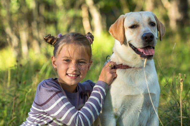 Lycklig liten flicka med hennes hund Förälskelse royaltyfri fotografi