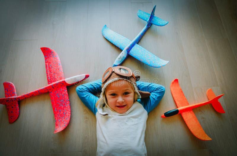 Lycklig liten flicka med hjälm- och exponeringsglaslek med leksaknivåer royaltyfri bild
