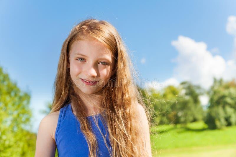 Lycklig liten flicka med långa lockiga hår utanför royaltyfria bilder