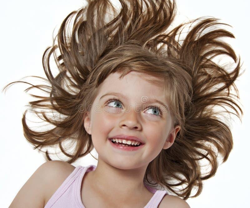 Lycklig liten flicka med långt trevligt wavy brunt hår royaltyfri bild