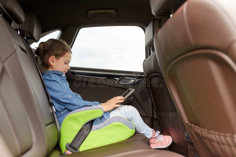 Lycklig liten flicka med minnestavlaPC:n som kör i bil arkivfoto