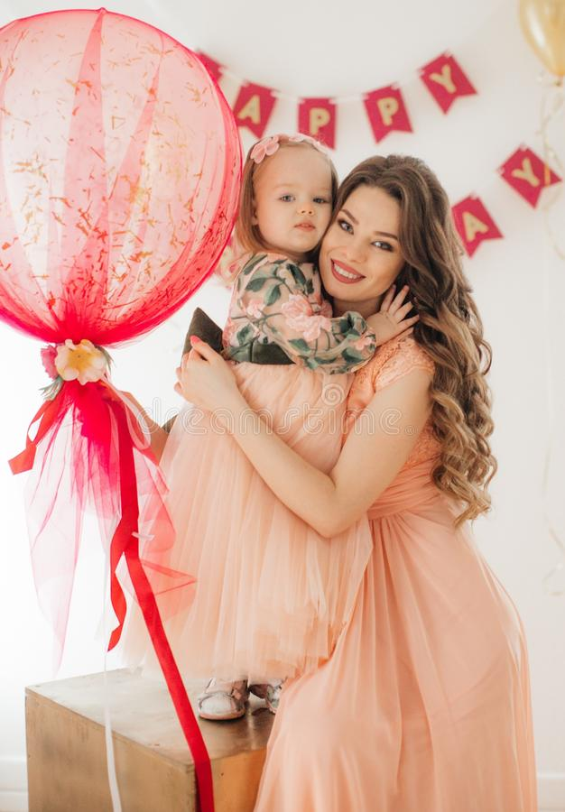 Lycklig liten flicka med modern som firar födelsedagpartiet arkivfoto