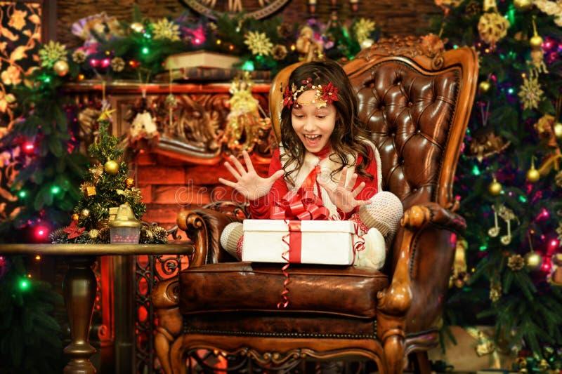 Lycklig liten flicka med sammanträde för gåvaask arkivfoto