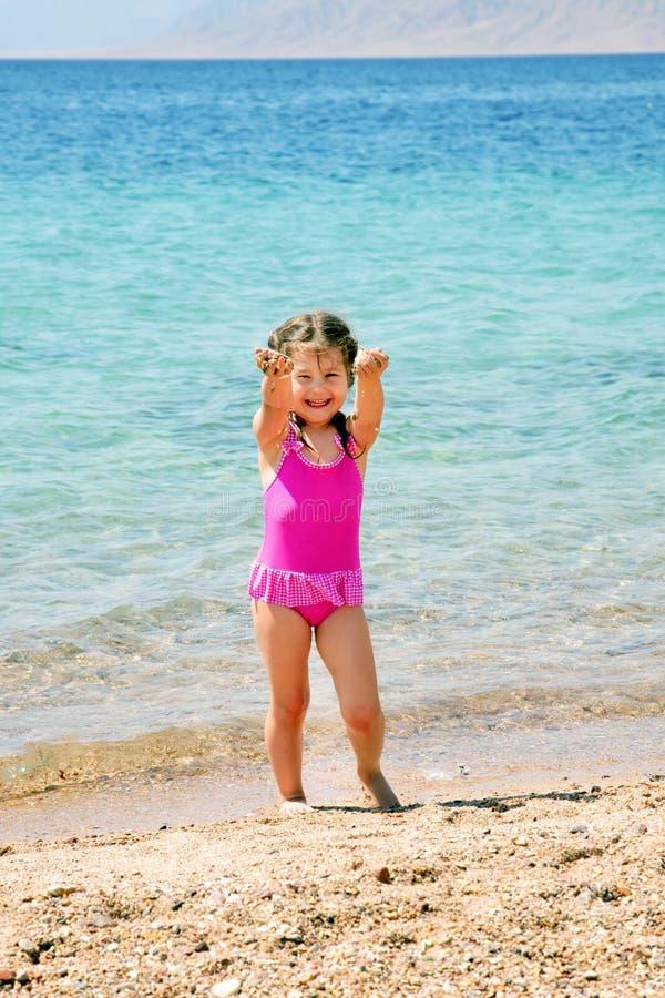 Lycklig liten flicka på spela för strand royaltyfri fotografi