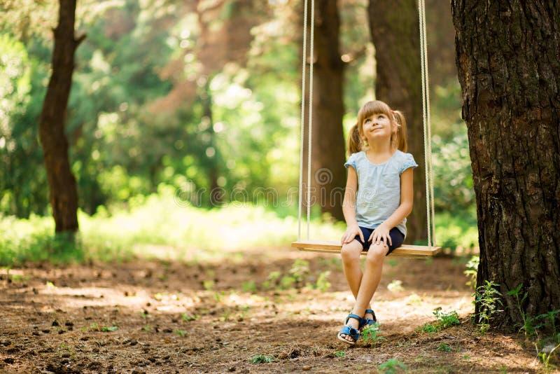 Lycklig liten flicka p? en gunga i parkera royaltyfri foto