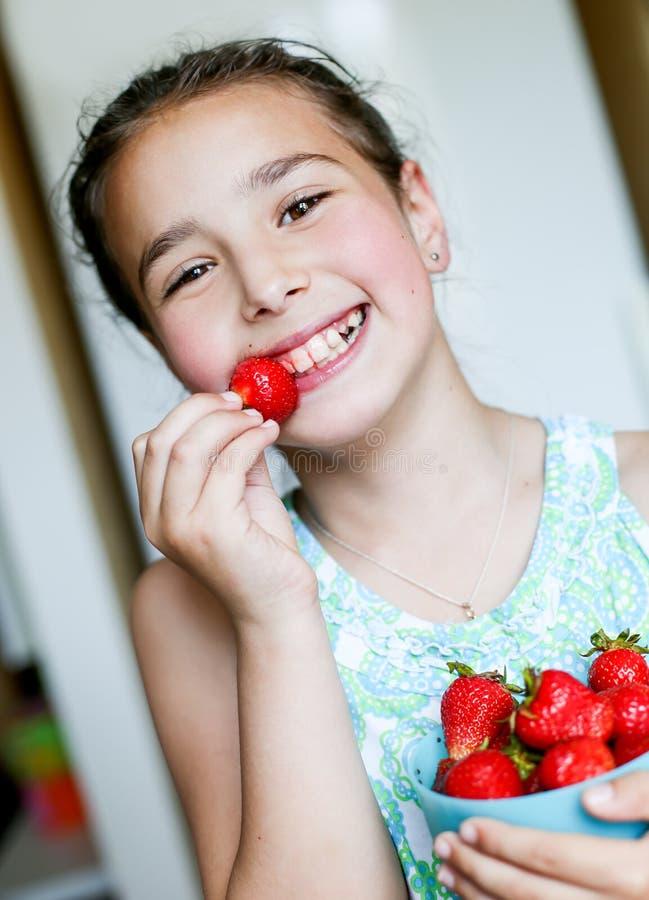 Lycklig liten flicka som äter jordgubbar arkivfoto