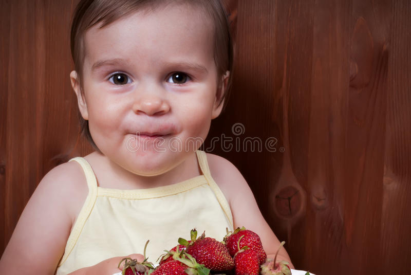 Lycklig liten flicka som äter jordgubbar fotografering för bildbyråer