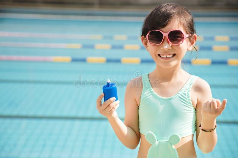 Lycklig liten flicka som applicerar sunscreenlotion på näsa royaltyfria bilder