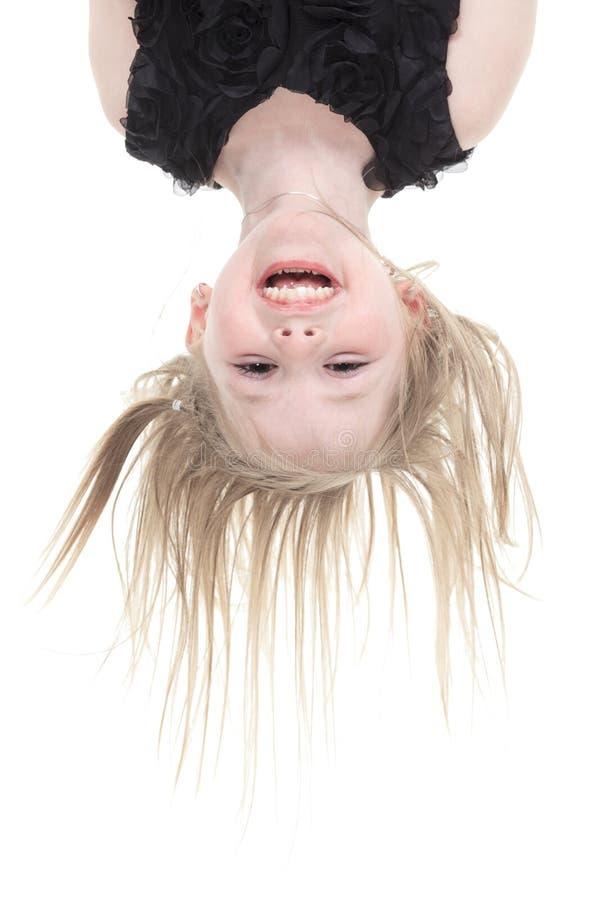 Lycklig liten flicka som hänger uppochnervänt som isoleras på royaltyfria foton