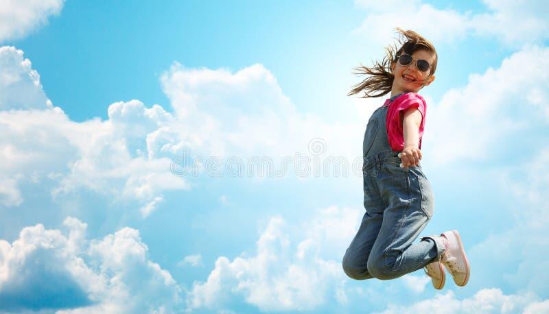 Lycklig liten flicka som högt hoppar över blå himmel royaltyfri foto