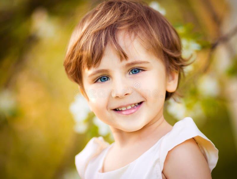 Lycklig liten flicka som har gyckel i den blommande vårträdgården arkivbild