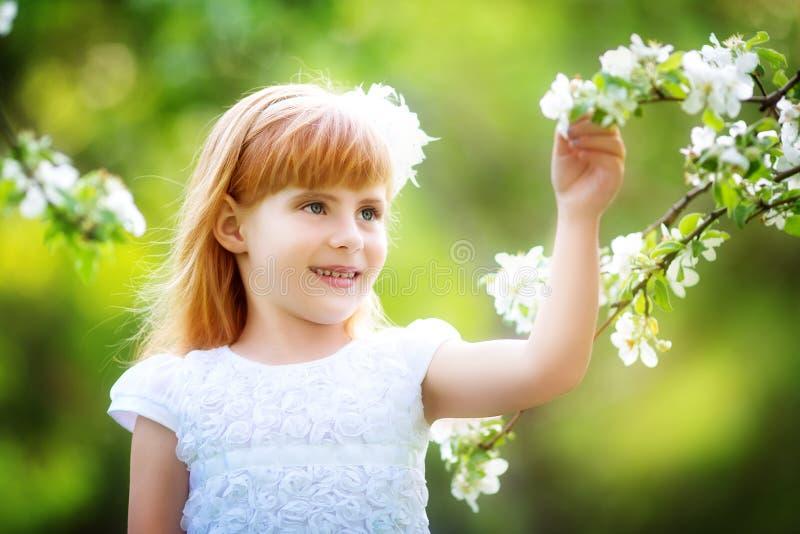 Lycklig liten flicka som har gyckel i den blommande vårträdgården fotografering för bildbyråer