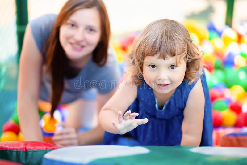 Lycklig liten flicka som har gyckel i färgglad plast- bollpöl med hennes moder royaltyfria bilder