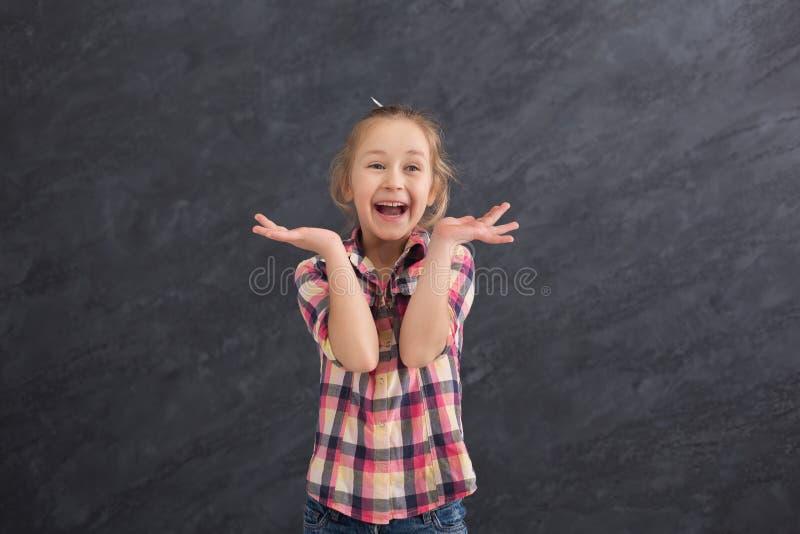 Lycklig liten flicka som har gyckel på grå bakgrund royaltyfri fotografi