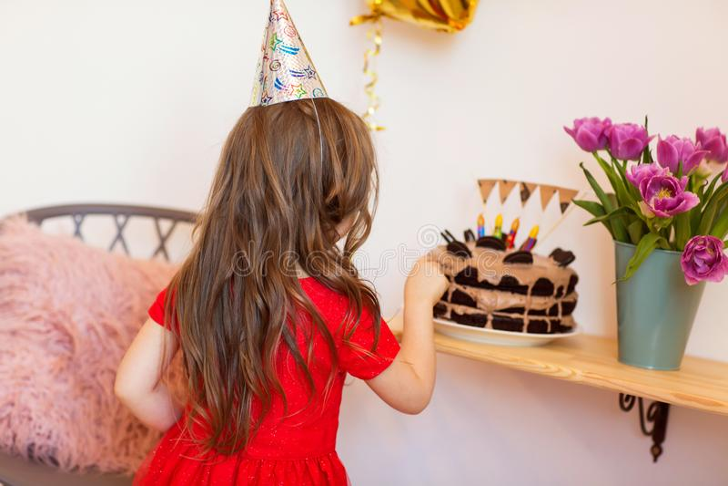 Lycklig liten flicka som hemma firar den fjärde födelsedagen arkivbild